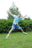 Jumping boy on a green background — Stock Photo