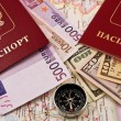 Passport with money, a map and compass — Stock Photo