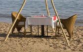 Dinner table on the beach — Stock Photo