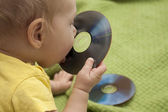 Baby is playing with cd or dvd disk — Stock Photo