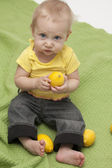 Baby eating a lemon on green background — Stock Photo
