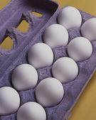 Dozen Eggs on Yellow Background — Stock Photo