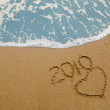 Year 2010 written on the sand - Stock Photo