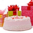 Pink pie with one candle and gifts - Stock Photo