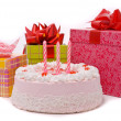 Pink pie with three candle and gifts — Stock Photo