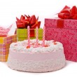 Pink pie with three candle and gifts - Stock Photo