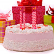 Pink pie with four candles and gifts — Stock Photo