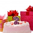 Pink pie with one candle and gifts — Stok fotoğraf #1657185