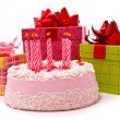 Pink pie with nine candles and gifts — Stock Photo