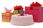 Růžový koláč s svíčku a dary v krabicích — Stock fotografie