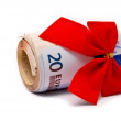 Roll of Euro money and red bow — Stock Photo