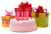 Pink pie with ten candles and gifts — Stock Photo