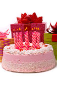 Pink pie with eleven candles and gifts — Stock Photo