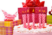 Pink pie with candles and gifts in boxes — Stock Photo
