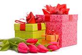 Tulipanes rojos y caja de regalo en un blanco — Foto de Stock