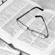Stock Photo: Glasses on opened dictionary