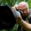 Photographer with telescopic lens. — Stock Photo #1393437