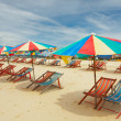 Happy parasols on empty beach — Stock Photo