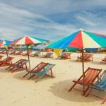 Happy parasols on empty beach — Stock Photo