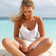 Woman in meditation on white sand beach. — Stock Photo