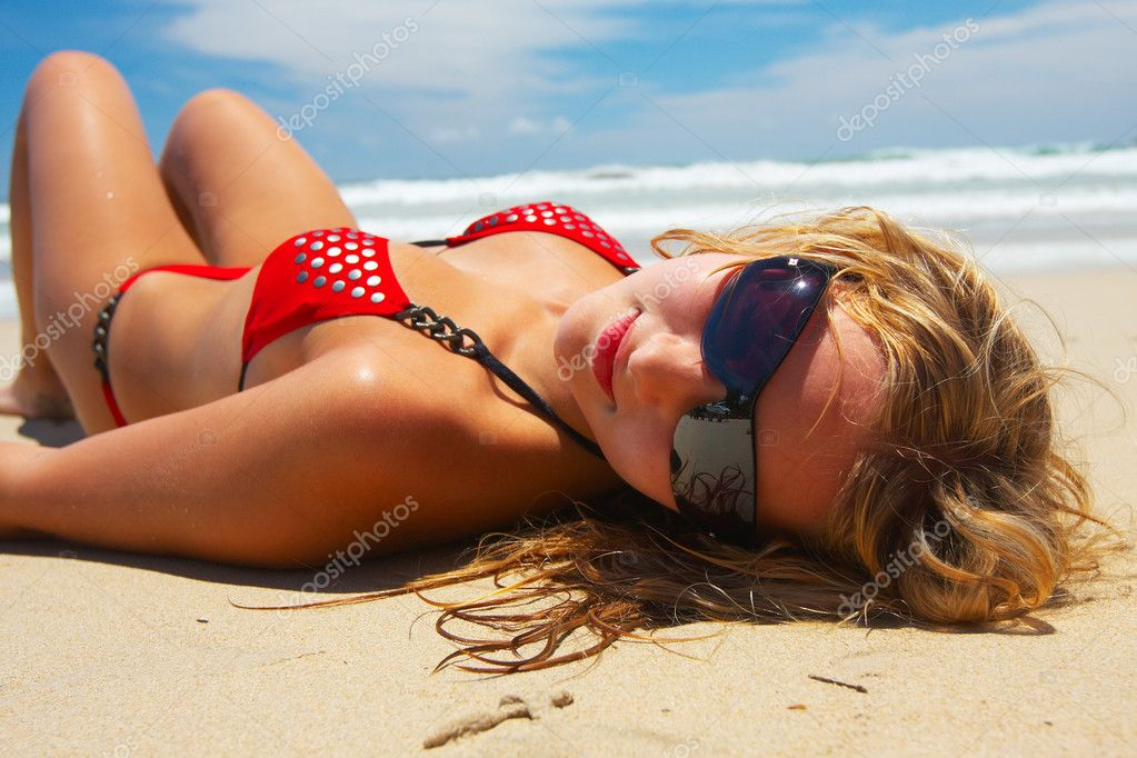 Young girl in red bikini is lying on white sand beach  Stock Photo #1393646