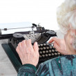 Grandmother with antique typewriter — Stock Photo