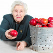 Grandma with red apples. — Stock Photo