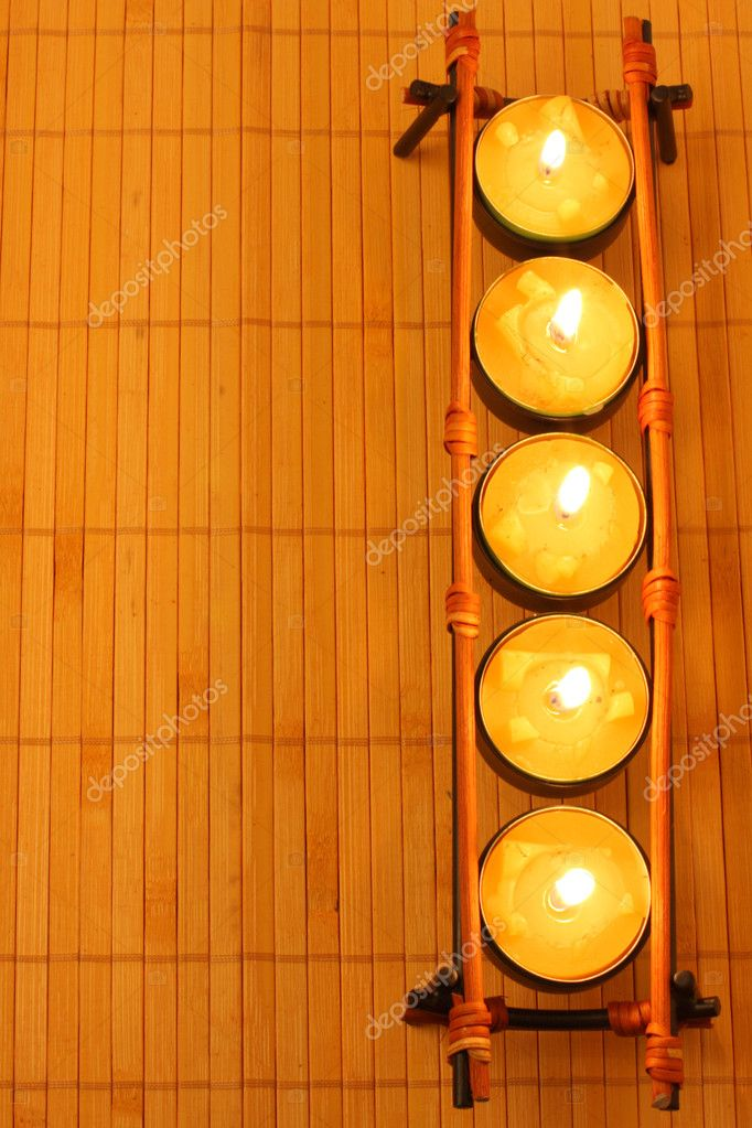 Row of candles on bamboo rug — Stock Photo #1416489