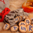 Stock Photo: Runes with pouch and candle close-up
