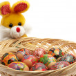 Easter rabbit with basket of easter eggs — Stock Photo
