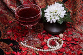 Still life with wine, flowers and pearls — Stock Photo