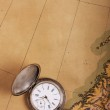 Old silver watch on ancient map — Stock Photo