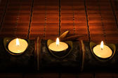 Candles on bamboo rug — Stock Photo