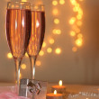 Two glasses of champagne and a gift — Stock Photo