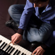 A young man playing on a synthesizer — Stockfoto