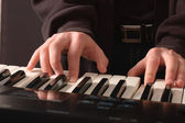 Beautiful men's hands on the keys — Stock Photo