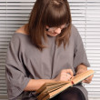 Brunette girl with glasses reading — Stock Photo