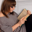 Brunette girl with glasses reading — Stock Photo #1755411