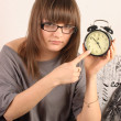 Foto Stock: Girl in glasses with alarm clock