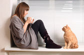 Girl with a cup of cappuccino and a cat — Stock Photo