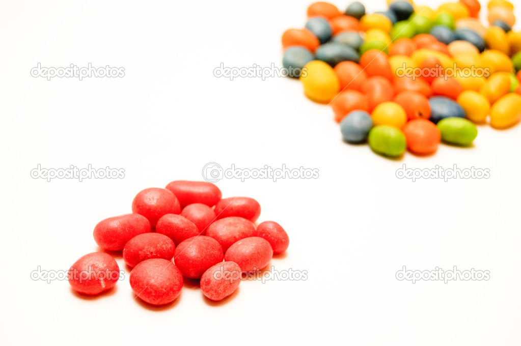 A handful of red candies in the foreground and the colorful candies in the background — Stock Photo #1918492