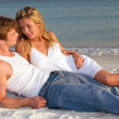 Stock Photo: Couple Lay On Beach At Sunset