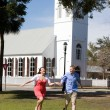 Couple Running By Church - Stock Photo