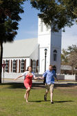 Couple Running By Church — Stock Photo