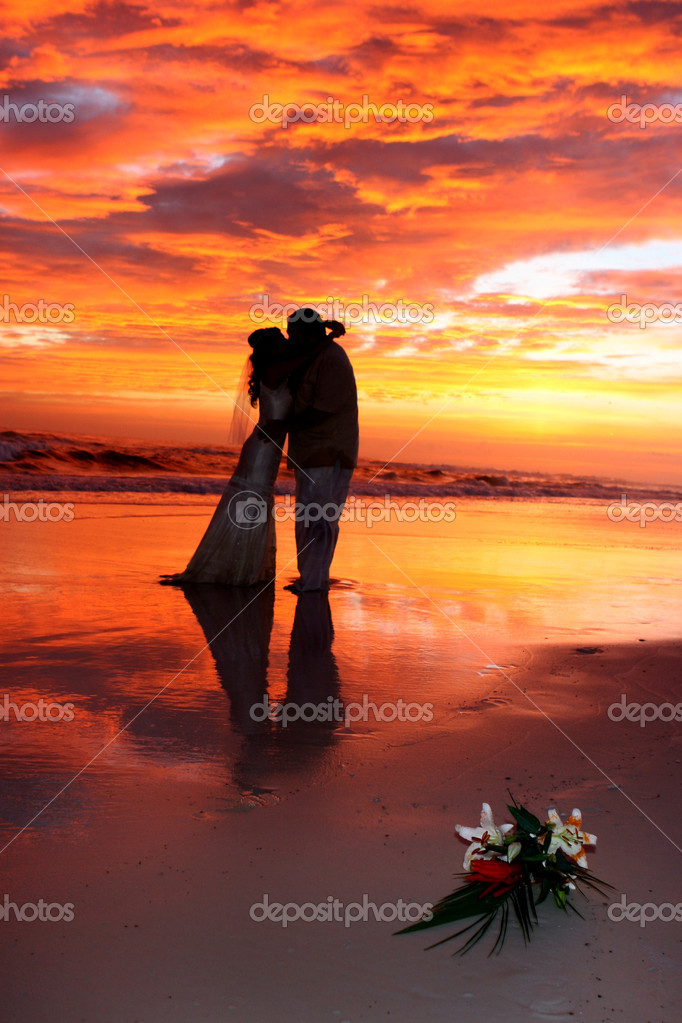 A bride and groom kiss on the beach during a spectacular sunset. — Stock Photo #1395814