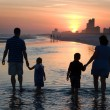 Young Family Silhouetted By Sunset — Stock Photo