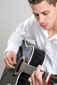 Young Man Strums Acoustic Guitar — Stock Photo