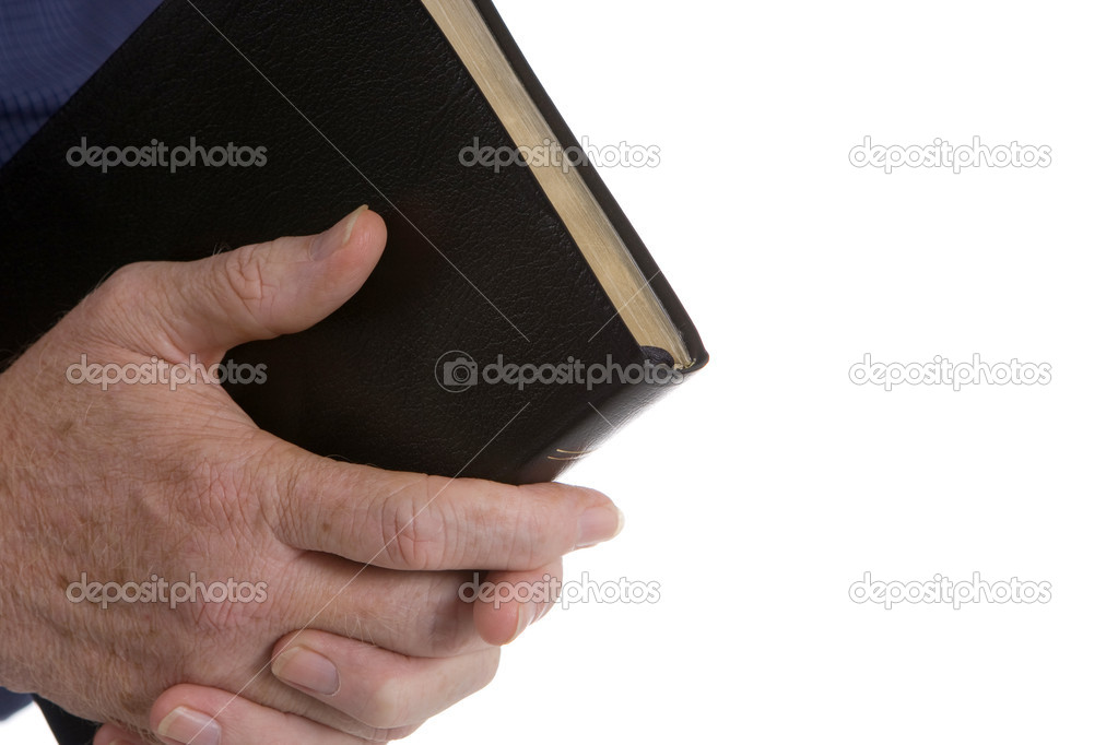 Interlaced hands of a mature man hold bible. Room for copy on right side.  Stock Photo #1412862