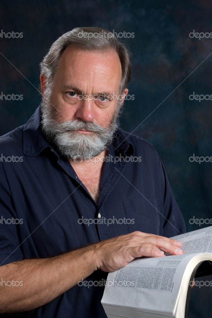 Mature man poses with a serious look with his hand on the bible. — Stock Photo #1413116