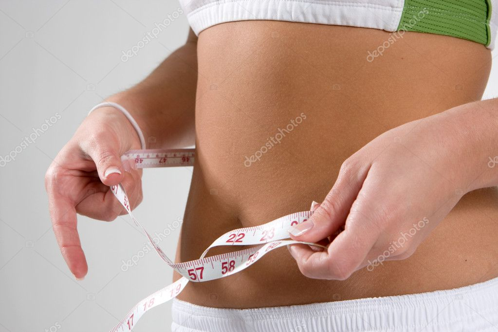 Fit young woman checks her waist size with a cloth tape measure.  — Stock Photo #1413118